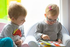 Boy and girl twins reading book. Together at home royalty free stock image