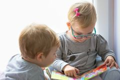 Boy and girl twins reading book. Together at home stock image