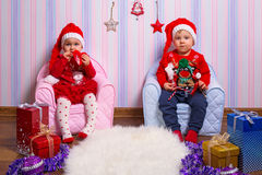 Boy and girl twins in santa helper costumes. Boy and girl twins posing with Christmas presents royalty free stock photos
