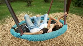 Boy and girl, twins swinging on a swing a hammock on the amusement park in the city. 4k, copy space stock video footage