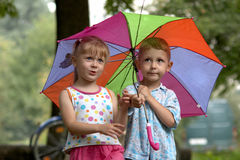 Boy and girl with umbrella Stock Photos