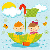 Boy and girl on the umbrella. Little boy and girl floating in a puddle by the umbrella Stock Image