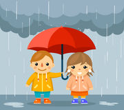 Boy and girl with umbrella standing under rain Stock Images