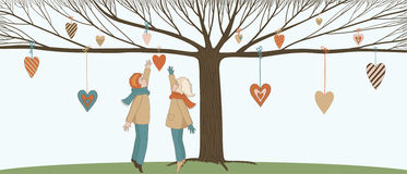 Boy and Girl under Love Tree. With hanging hearts Royalty Free Stock Image