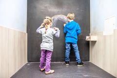 Boy and girl using chalkboard royalty free stock photography