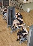 Boy and a girl using excercise machines Stock Image