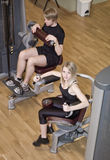 Boy and a girl using excercise machines Stock Photo