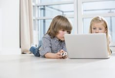 Boy and girl using laptop on floor at home Stock Photography