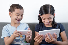 Boy and girl using mobile and tablet digital. Royalty Free Stock Photography
