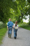 Boy And Girl Walking On Country Lane Royalty Free Stock Photo