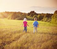 Boy and girl walking on the field in summer stock photos