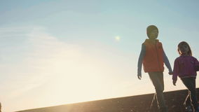 Boy and girl walking outside at sunset stock video footage