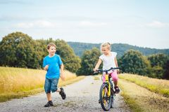 Boy and girl walking and riding bicycle on a dirt path Royalty Free Stock Photography
