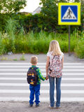 Boy and girl want to cross the road at a pedestrian crossing Royalty Free Stock Images