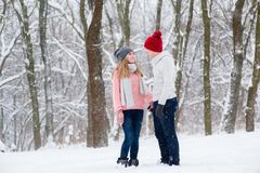 Young couple in winter forest. Boy and girl in warm sweaters and jeans hug and kiss at winter snow background Royalty Free Stock Photography