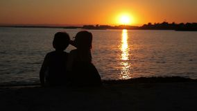 Boy and girl are watching the sunset over the sea. Boy and girl watching the sunset over the sea while sitting on the beach stock video footage
