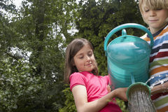Boy And Girl Watering Garden Royalty Free Stock Photo