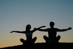 Boy and girl waving their hands at sunset. Stock Image