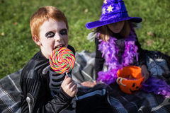 Boy and girl wearing halloween costume with candies. Skeleton. Witch Stock Photo