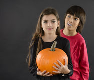 boy and girl wearing halloween costume with pumpkin on black ba stock photos