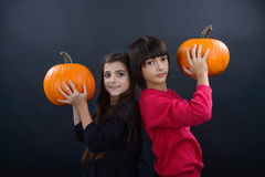 Boy and girl wearing halloween costume with pumpkin on black  ba Royalty Free Stock Image