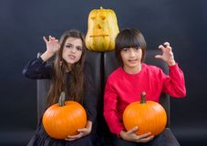 Boy and girl wearing halloween costume with pumpkin on black  ba Stock Image
