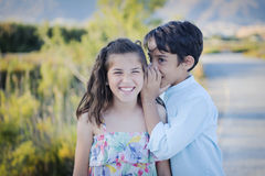 Boy and girl whispering Royalty Free Stock Image