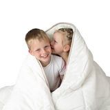 Boy and girl whispering under blanket Stock Photo