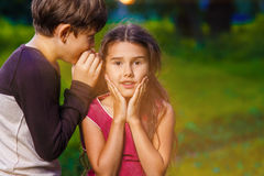 Boy girl whispers in the ear secret rumors says in Stock Photography