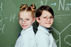 Boy and girl in white coats and protective eyeglasses standing together near chalkboard and smiling at camera Royalty Free Stock Photography