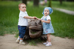 Boy and girl with wooden crocodile Stock Images