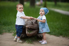 Boy and girl with wooden crocodile Royalty Free Stock Photos