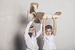 Boy and girl with wooden model airplane and a cap with cap desig Stock Image