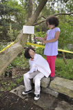 Boy and girl in the woods with hair clippers. Multiracial brother and sister in the woods with hair clippers Royalty Free Stock Photos