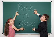 Boy and girl write back to school on board Royalty Free Stock Photos