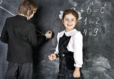 Boy and girl writing on blackboard Royalty Free Stock Photos