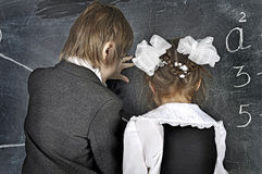Boy and girl writing on blackboard Royalty Free Stock Images