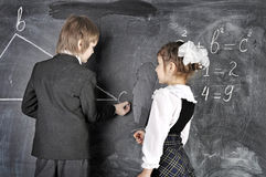 Boy and girl writing on blackboard Royalty Free Stock Photo