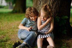 Boy with girl of 7-8 years sit under an old tree and excitedly look at the laptop screen. Stock Photography