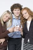 Boy & girls / a glass of champagne. Two girls and a boy are standing together, holding glasses of wine and girls are leaning their heads on the boys shoulders Royalty Free Stock Photo