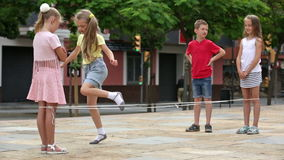 Boy and girls having fun with chinese jumping rope. Cheerful boy and girls in elementary school age having fun with chinese jumping rope stock footage