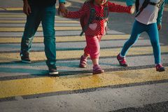 Boy and girls holding hands go to school crossing the road. Kids go school stock images
