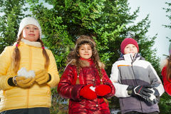 Boy and girls holding snowballs in their hands Stock Photo