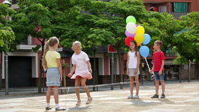 Boy and girls jumping rope. Cheerful boy and girls in elementary school age having fun with chinese jumping rope stock footage