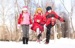 Boy and girls playing with snow in winter park Stock Photos