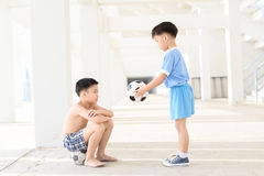 Boy give football. Young Asian boy give football to another boy in white building Stock Photo
