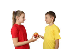Boy gives apple to girl Stock Image