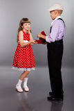 The boy gives beads to the girl. Retro style. Stock Photography