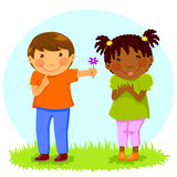Boy gives flower to girl. Caucasian boy gives a flower to an African girl Royalty Free Stock Photos
