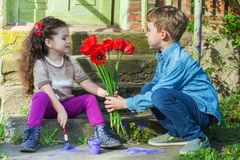 Boy gives flowers to baby girl Stock Photography